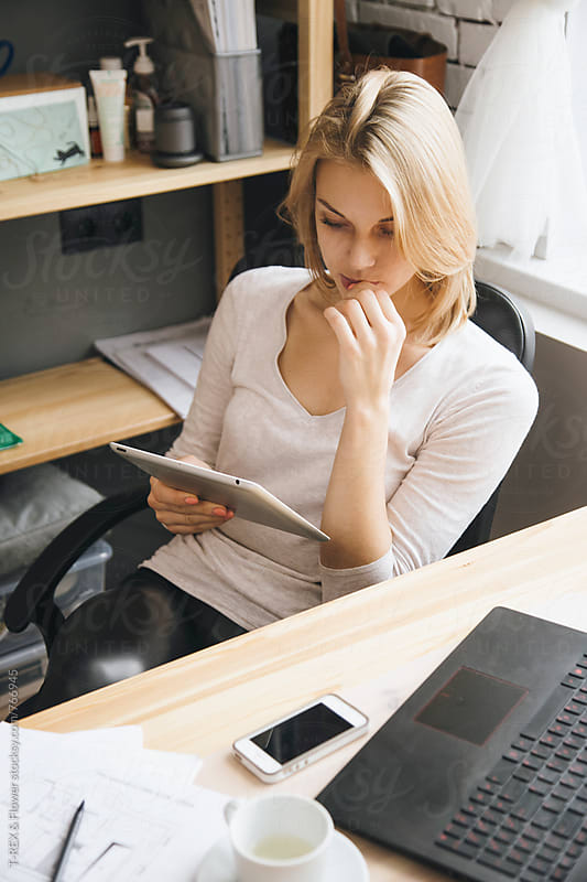 Young blonde woman using her tablet at work by T-REX & Flower for Stocksy United