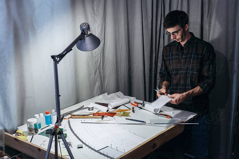 Artist creating stained glass window in his studio  by Jovana Milanko for Stocksy United