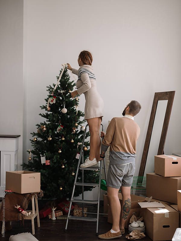 Couple Decorating Christmas Tree by Milles Studio for Stocksy United