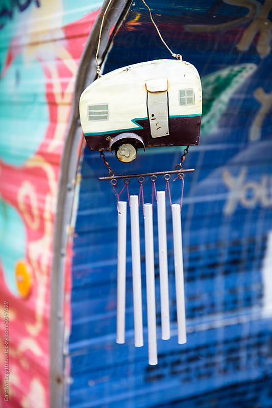 Camper wind chime hanging against a colorful trailer by Carolyn Lagattuta for Stocksy United