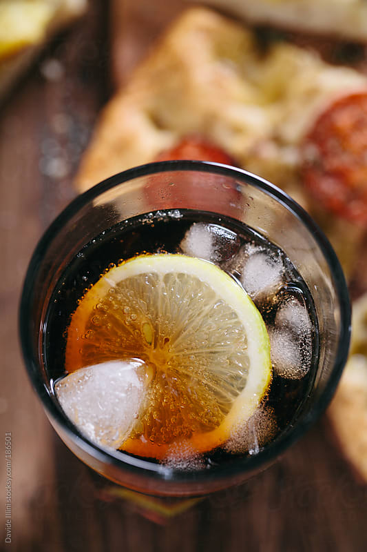Glass of Cola with Ice and Lemon by Davide Illini for Stocksy United