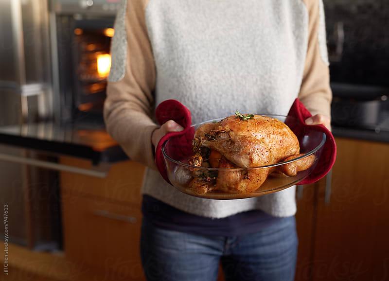 woman in kitchen holding roast chicken by Jill Chen for Stocksy United