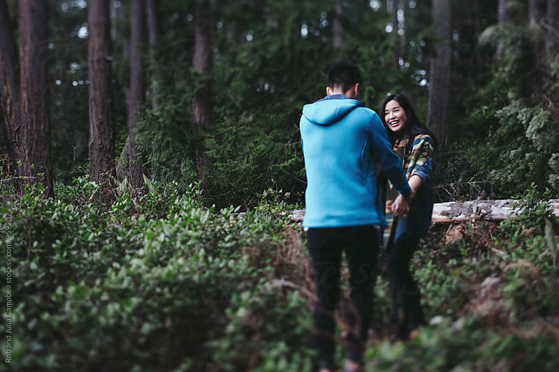 Young asian couple spending quality time together outside in nature by Rob and Julia Campbell for Stocksy United