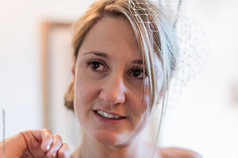 Portrait of a bride wearing a veil made of netting. by Holly Clark for Stocksy United