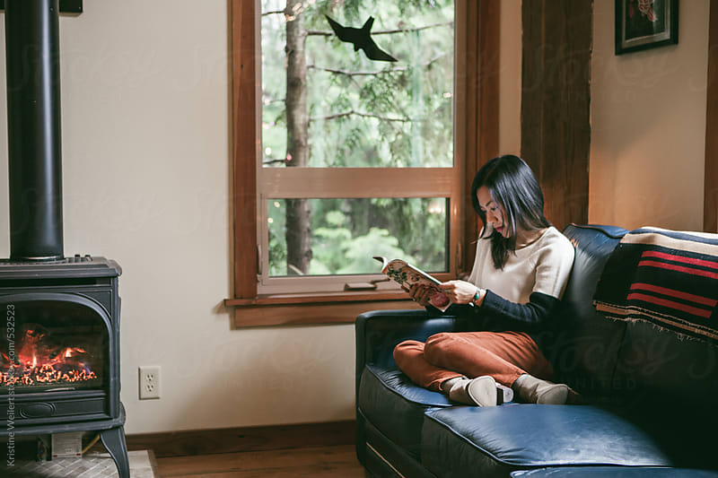 Woman reading a magazine on her blue leather couch in a cabin by Kristine Weilert for Stocksy United