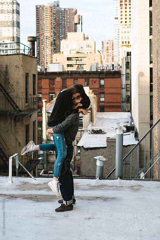 Young couple having fun on a rooftop in the city by WAVE for Stocksy United