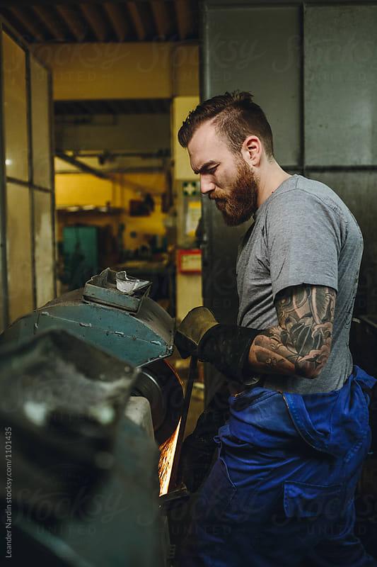 tattoed metal worker grinding metal plate in a workshop by Leander Nardin for Stocksy United