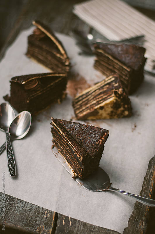 Slices of chocolate cake on the baking paper by Brkati Krokodil for Stocksy United