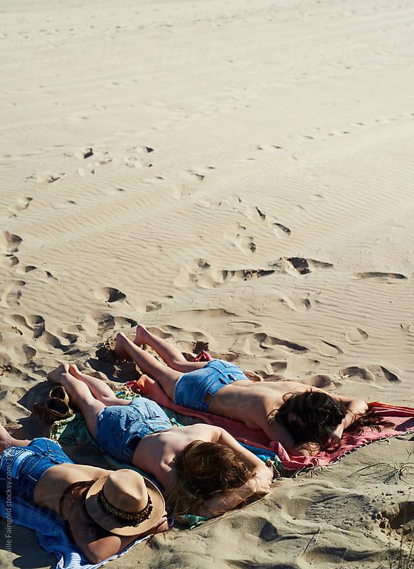 Girls of beach blanket sunbathing by Guille Faingold for Stocksy United