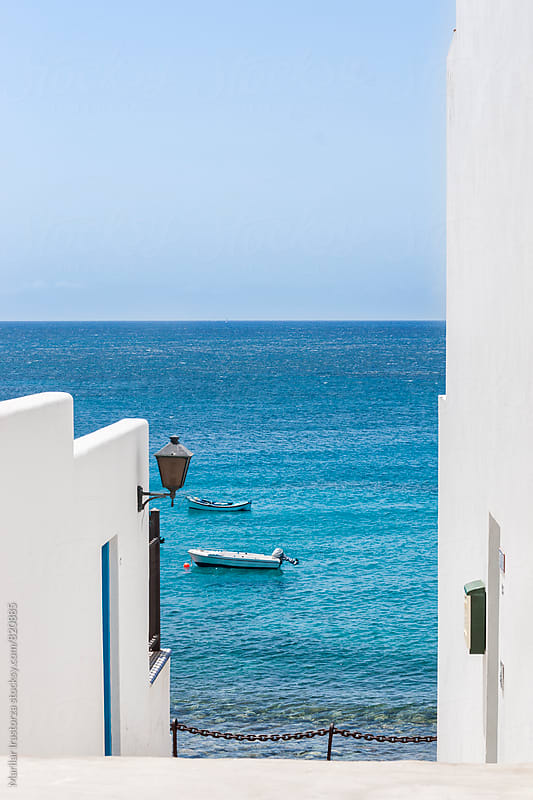 View of the sea between two white houses by Marilar Irastorza for Stocksy United