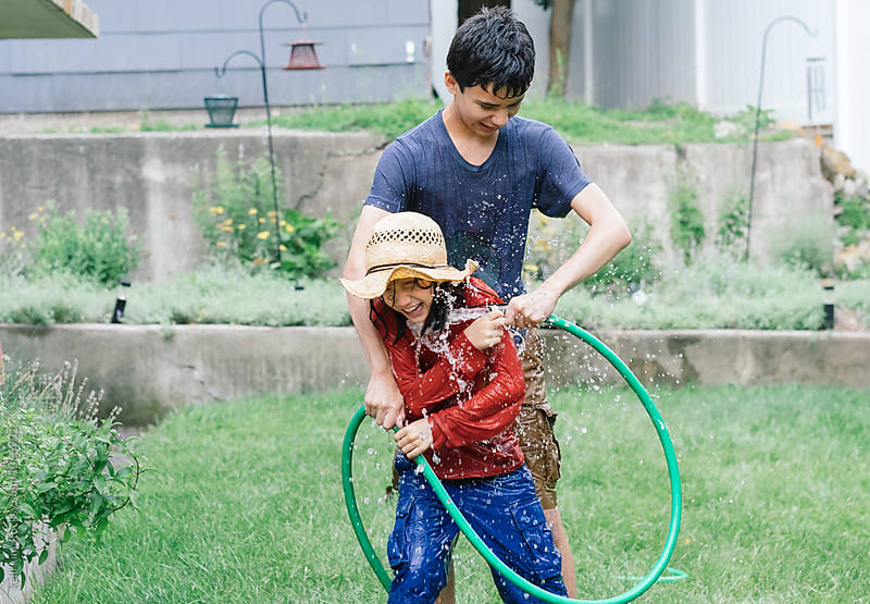 Brothers having water fight with hose by Kelli Seeger Kim for Stocksy United