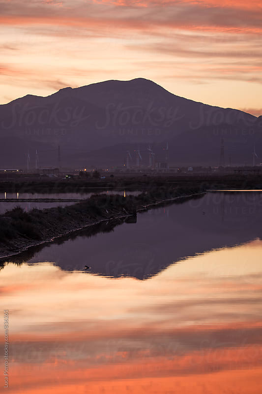 Mountain reflected in a lake at sunset by Luca Pierro for Stocksy United