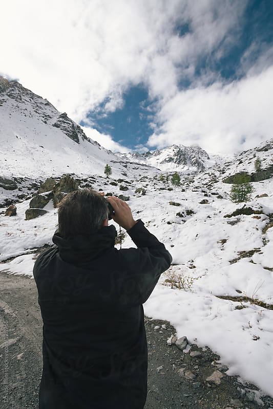 Man looking mountains through binoculars. by Davide Illini for Stocksy United