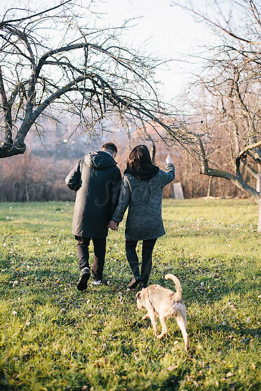 Couple taking a walk in nature with their dog by Marija Mandic for Stocksy United