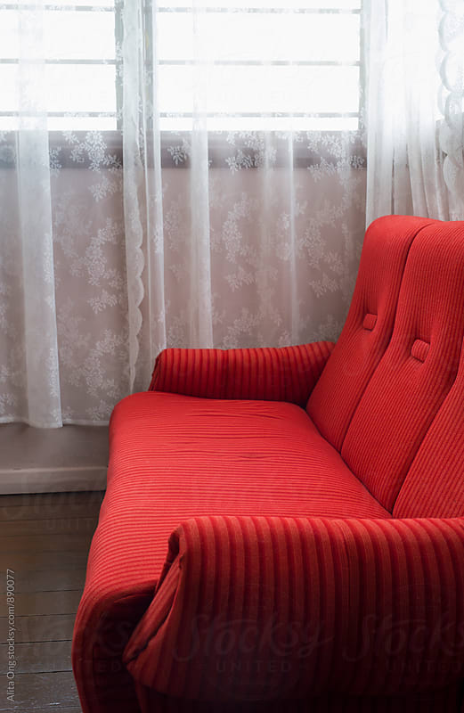 Red couch by Alita Ong for Stocksy United