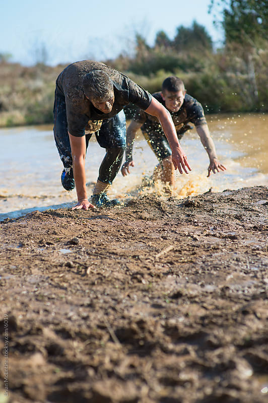 Two Men Run Through Water Obstacle on Mud Run Course by Brian McEntire for Stocksy United