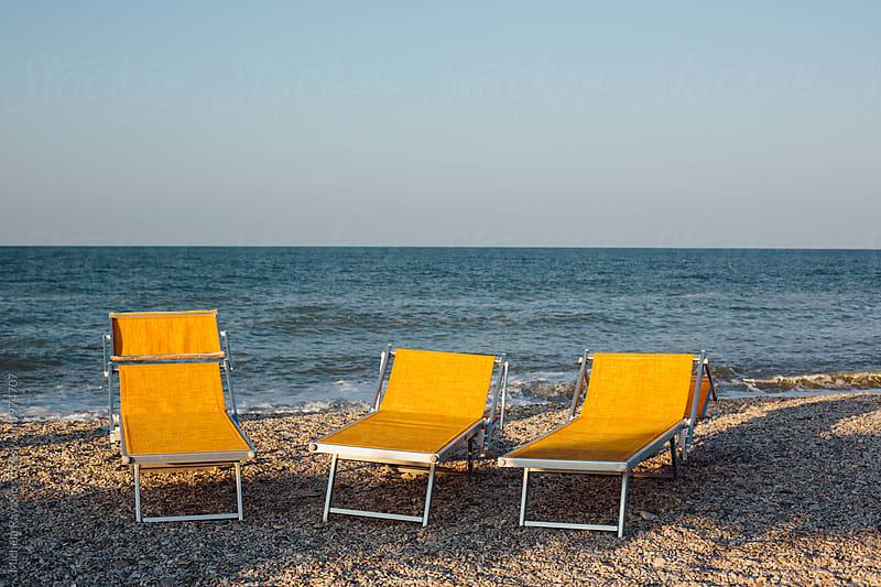 Three yellow sunbeds on the shore at sunset by michela ravasio for Stocksy United