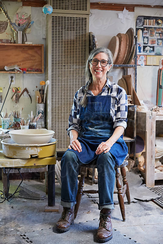 Portrait of senior woman with grey hair inside her pottery studio by Trinette Reed for Stocksy United
