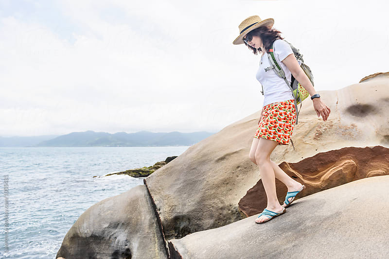 Female backpacker in sunhat walking on rock by Lawren Lu for Stocksy United