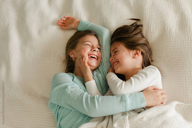 Sisters laying in bed giggling together by Amanda Worrall for Stocksy United