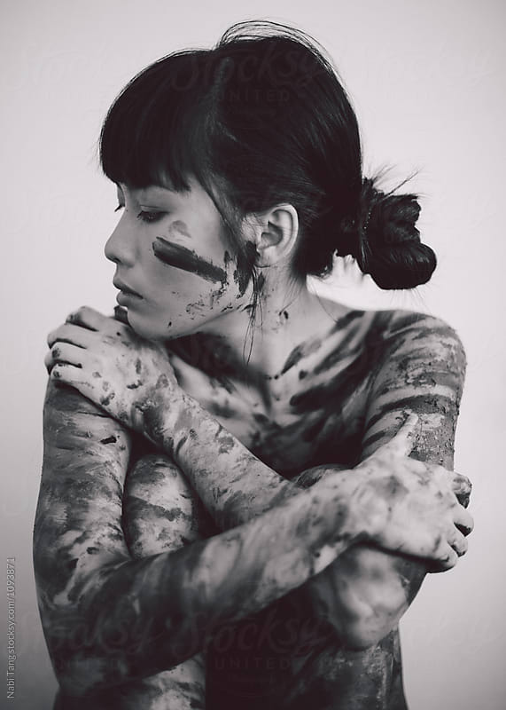 Black and white portrait photo of young beautiful Asian woman with messy paint on the body