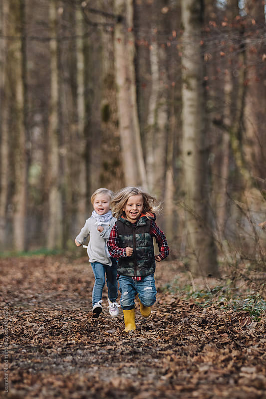 little boy and girl play tag in autumnal forest by Leander Nardin for Stocksy United