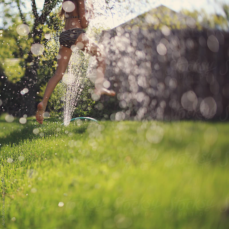 Girl Having Fun And Running Through The Sprinkler On A Hot Summer Day by ALICIA BOCK for Stocksy United