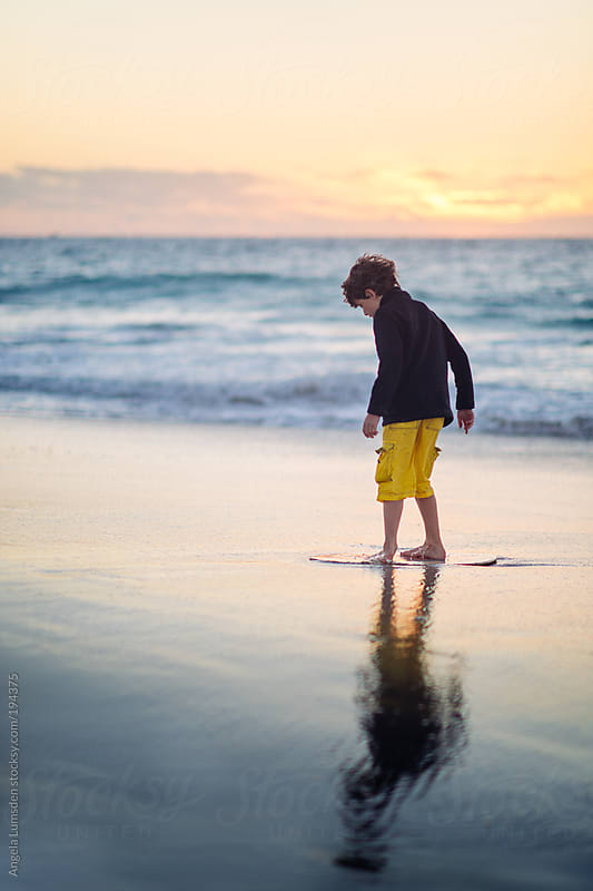 Boy catching a last ride on his skim board in twilight at the beach by Angela Lumsden for Stocksy United