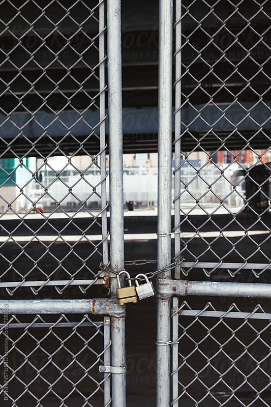 Fence door closed by two padlocks. by BONNINSTUDIO for Stocksy United