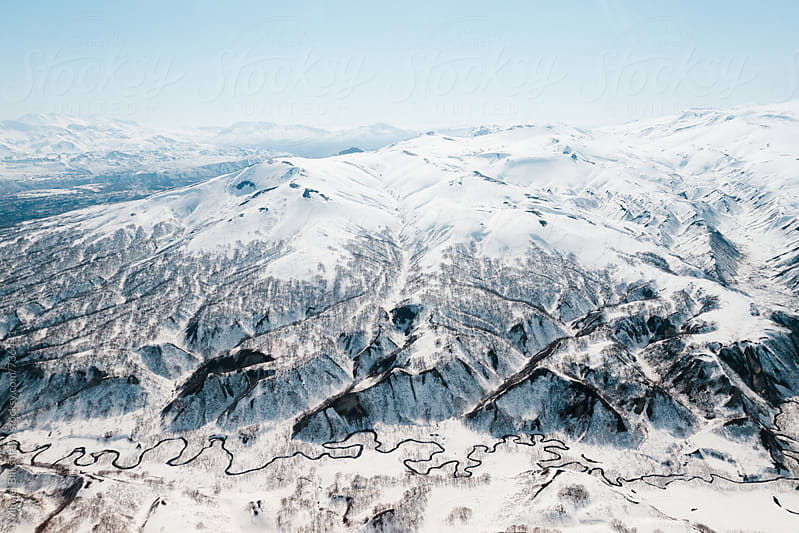 Aerial view of snow-covered mountains and a meandering river by Mihael Blikshteyn for Stocksy United
