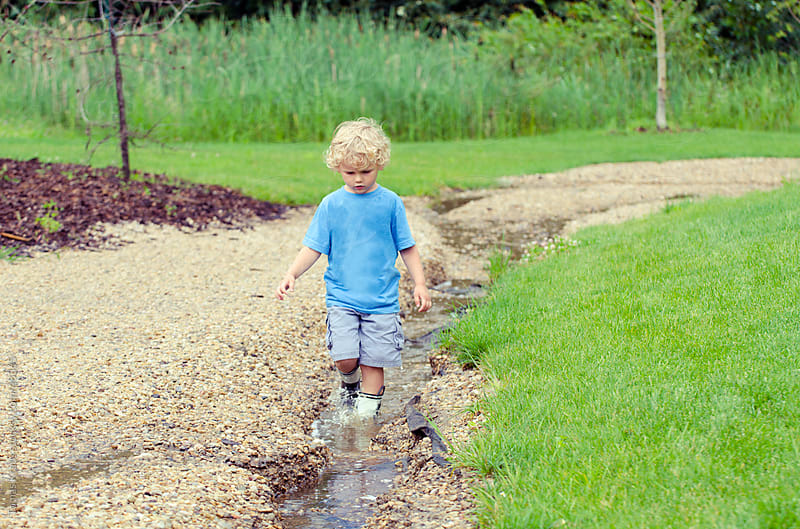 young boy walking in puddle by Tomas Kraus for Stocksy United