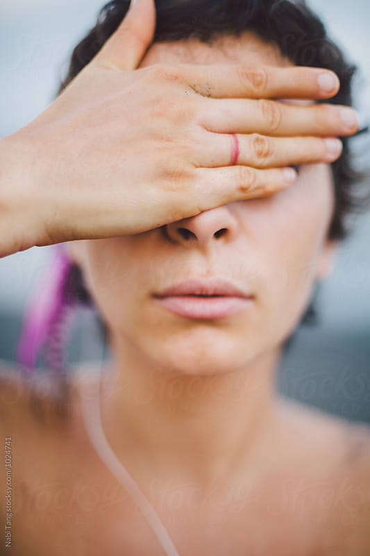 Woman covering her eyes by Nabi Tang for Stocksy United