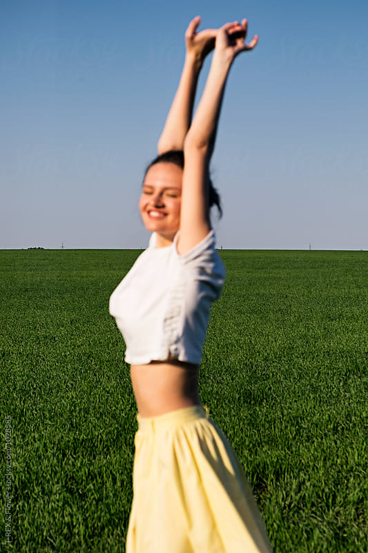 Girl stretching in sunlight against of green field and blue sky by Danil Nevsky for Stocksy United