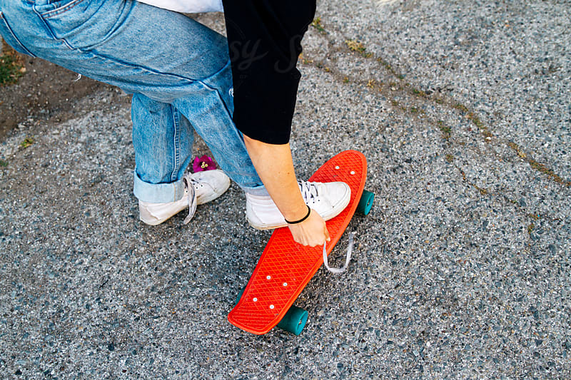 young woman reaches down to tie shoes while skatebaording by Jesse Morrow for Stocksy United