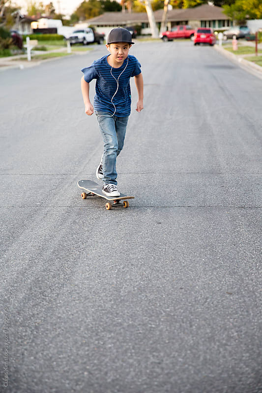 Asian boy riding his skateboard on the street by Curtis Kim for Stocksy United
