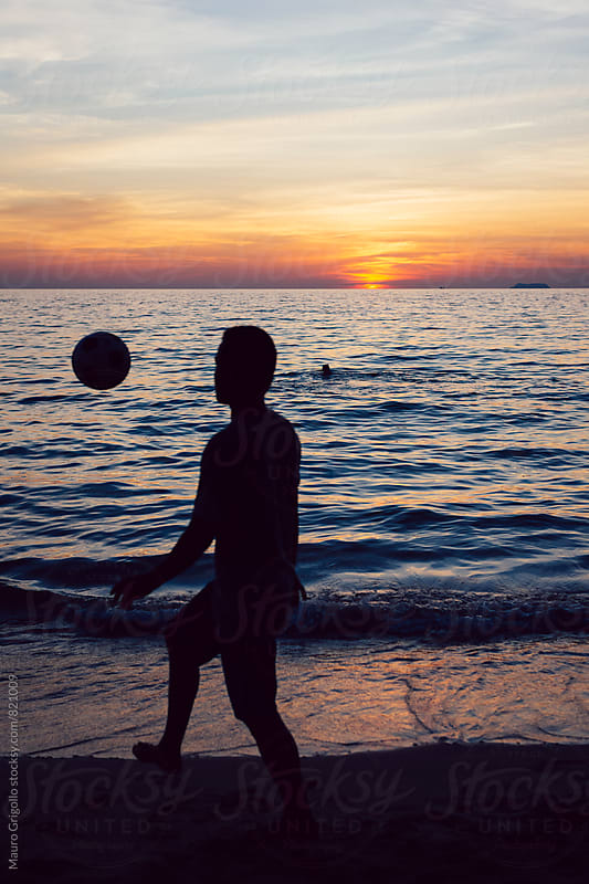 Man playing with a ball on the beach by Mauro Grigollo for Stocksy United