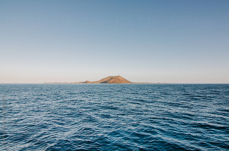 Volcanic Island surrounded by blue sea on a clear day by Darren Seamark for Stocksy United