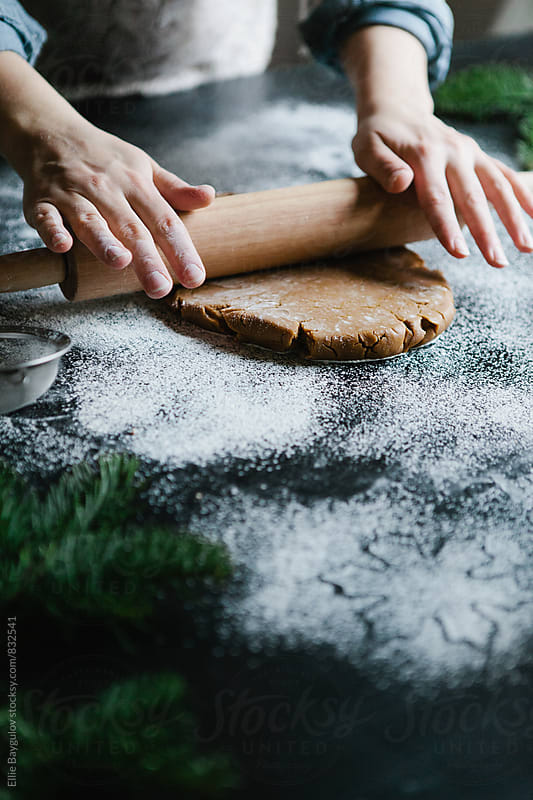 Woman rolling out cookie dough by Ellie Baygulov for Stocksy United