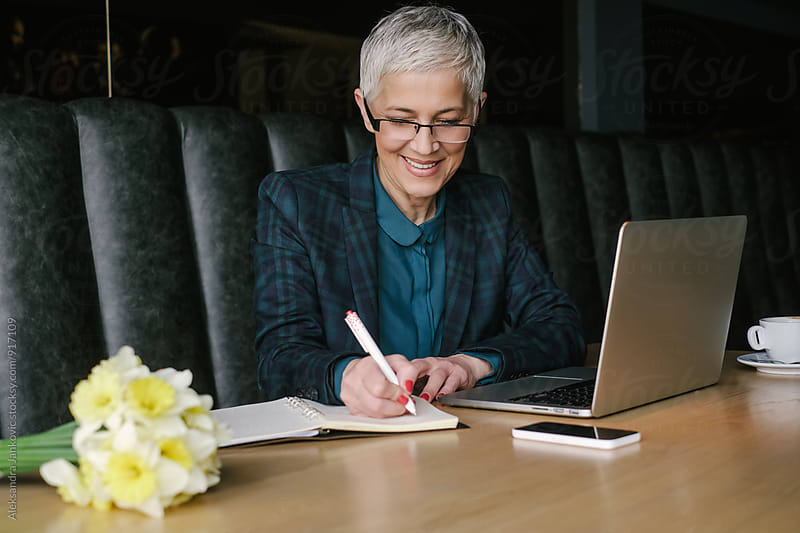 Smiling Senior Businesswoman Writing Notes while Working by Aleksandra Jankovic for Stocksy United