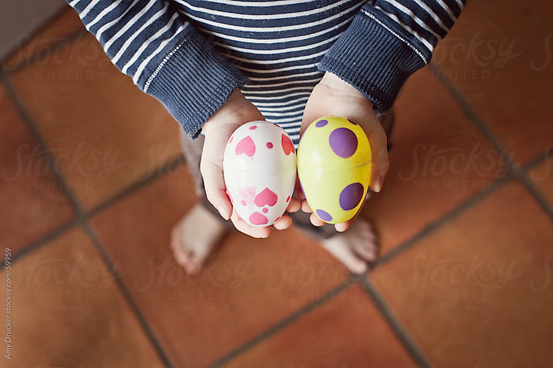 Child's Hands Holding Plastic Eggs by Amy Drucker for Stocksy United