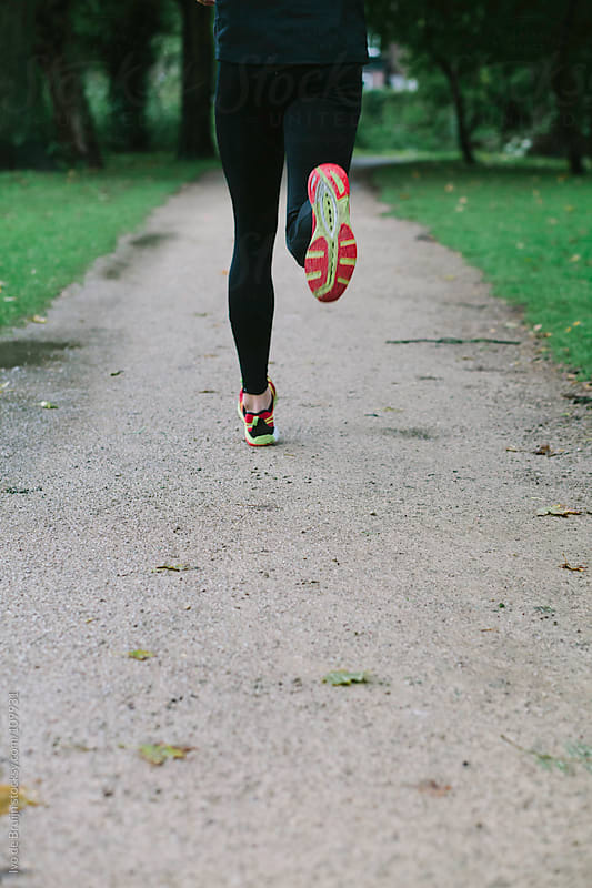 Photo of the legs of a man running on a gravel road in a park by Ivo de Bruijn for Stocksy United