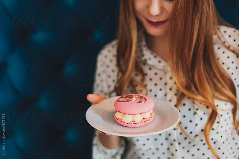 Young Woman Holding a Macaron  by Lumina for Stocksy United