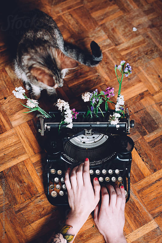 woman typing with a vintage typewriter with flowers and cat  by Thais Ramos Varela for Stocksy United
