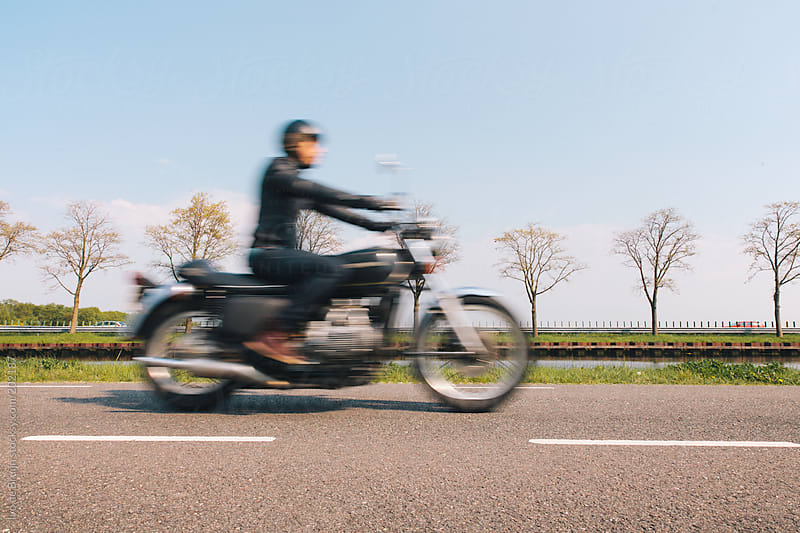 Blurry image of a rider or a motorcyclist on a classic motor by Ivo de Bruijn for Stocksy United