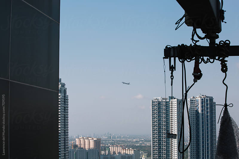 An airplane flies over the city as viewed from the rooftop of a building by Lawrence del Mundo for Stocksy United