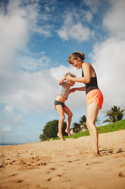 Pretty mom playing jumping games with  young girl jump on sandy tropical beach in summer by Rob and Julia Campbell for Stocksy United
