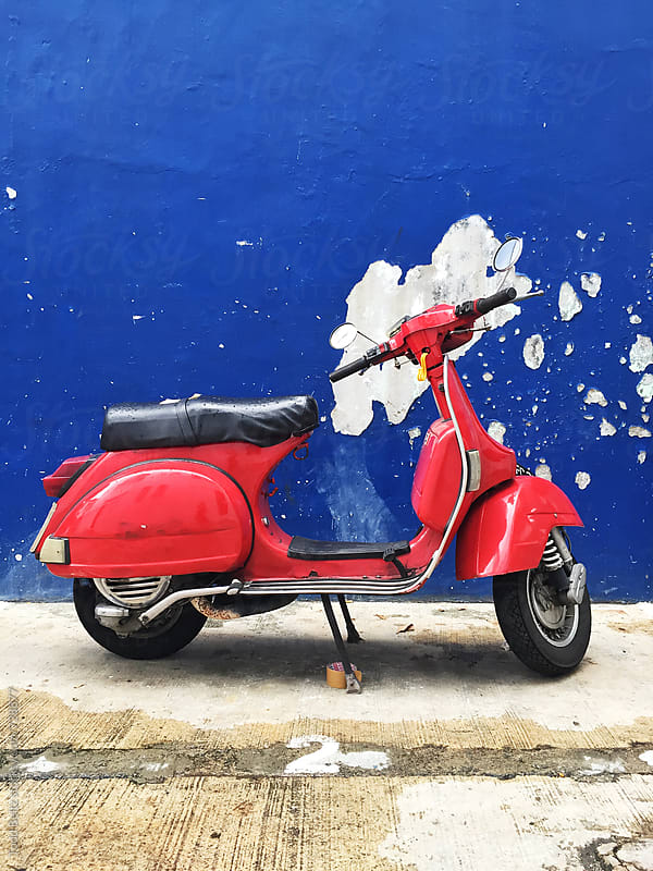 Vintage red scooter against blue wall by Todd Beltz for Stocksy United