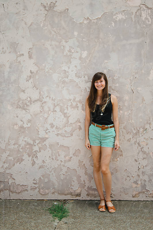 Teenaged Girl Smiling Against Urban Wall by michelle edmonds for Stocksy United
