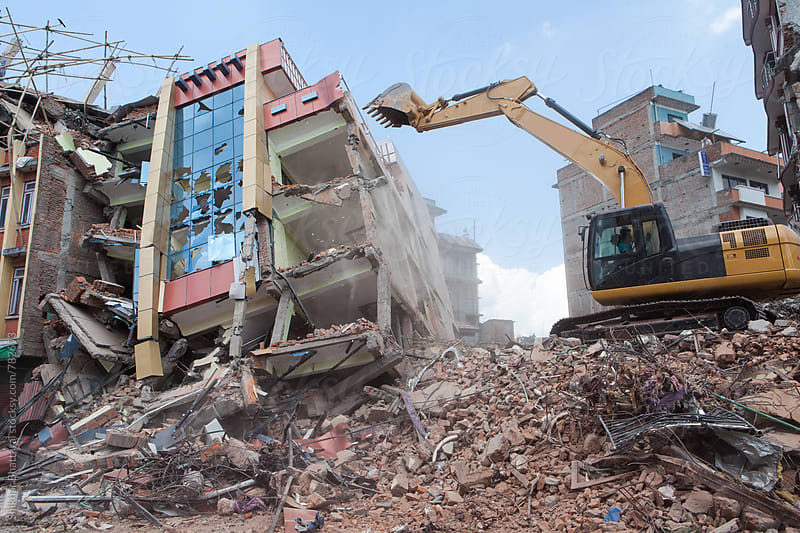 An excavator clearing off debris. by Shikhar Bhattarai for Stocksy United