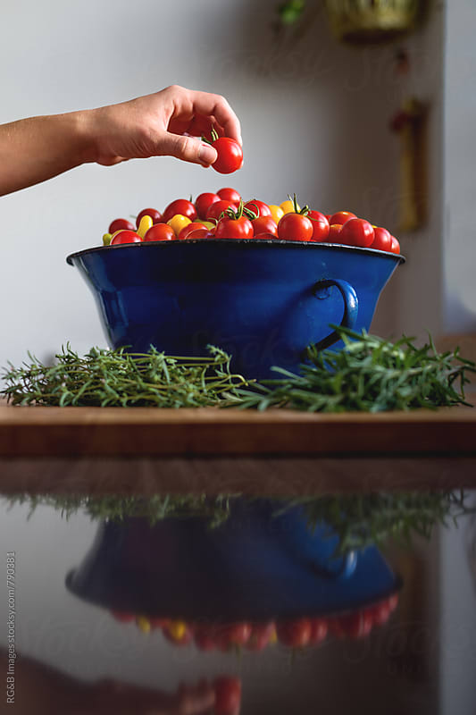 Woman picking up a cherry tomato from a blue pot by RG&B Images for Stocksy United